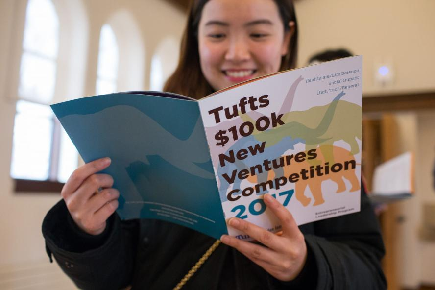 A student perusing the Tufts 100k Competition brochure