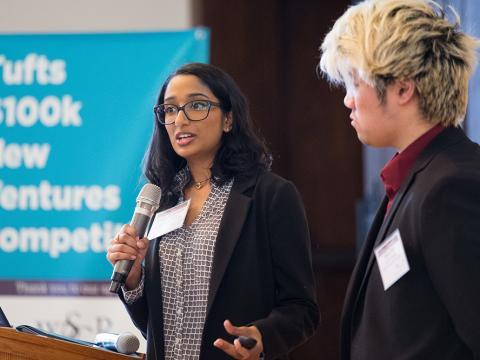 Photo of 2019 Tufts $100k New Ventures Competition student holding microphone at finals.