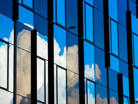 Photo of building on Tufts University's campus with reflection of cloud and birds