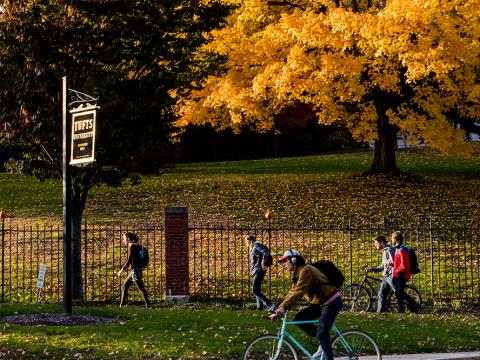 Photo of foliage during fall at Tufts University campus with bicyclist in foreground and people walking in background