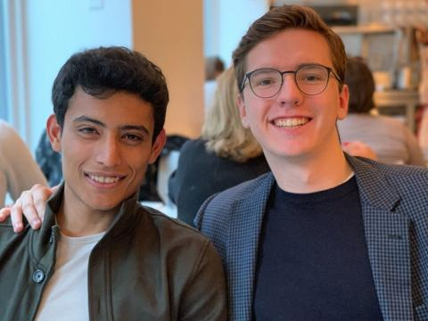 Photo of Shehryar Malik, A19 (pictured left), and Greg Kulchyckyj, A19 (pictured right) sitting down at a restaurant.