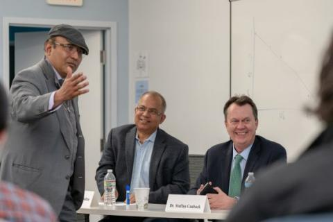 Partha Ghosh gestures with the panelists from his town hall